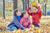 Children look at their mother who sits next and tries on crown made of yellow maple leaves