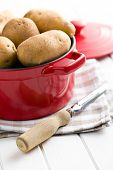 the uncooked potatoes and old wooden peeler