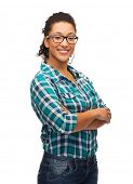 hapiness and people concept - smiling young african american woman in eyeglasses with crossed arms