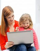 family, children, parenthood, technology and internet concept - happy mother and daughter with lapto