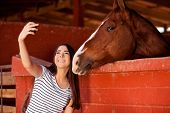 image of stable horse  - Beautiful young Hispanic woman taking a photo of herself and her horse at the stables - JPG