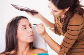 stock photo of eyebrow  - Female makeup artist darkening eyebrows with eyebrow pencil on Young Attractive woman - JPG