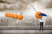 stock photo of newton  - Happy businessman holding umbrella against newtons cradle above city - JPG