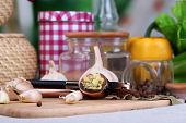 Composition with garlic press, fresh garlic and glass jars with spices on wooden table, on bright  b