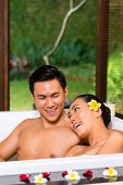 stock photo of scant  - Indonesian Asian couple in wellness beauty day spa having aroma therapy bath with essential oils or salt - JPG