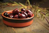 Kalamata olives into a bowl on wooden table