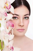 Close-up portrait of young beautiful woman with white orchid
