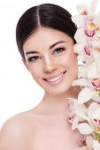 Young beautiful healthy smiling happy woman with white orchid over white background