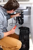 pic of plumber  - Young plumber fixing a sink - JPG