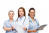 healthcare and medicine concept - calm female doctor adn nurses with clipboard and stethoscope givin