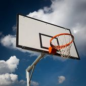 Basketball hoop against  lovely blue summer sky with some fluffy white clouds