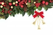 Christmas and winter background floral border with bells, red bauble decorations, holly, and winter greenery over white with copy space.