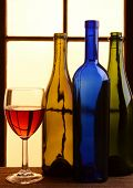 A wine still life with warm tones. Three different wine bottles and a glass of red wine in front of a window with warm sunlight.