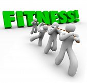 Fitness word in green 3d letters pulled by a team working together to exercise and gain physical strength and endurance