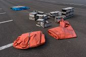 stock photo of tarp  - Orange tarp and broken boxes on a parking lot near the port - JPG