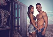 Fashion Photo Shoot. Two Sexy Couple Posing Flaunting Perfect Body Beside Old Wooden House