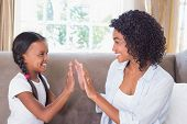 Pretty mother playing clapping game with daughter on couch at home in the living room