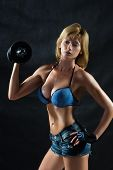 stock photo of breast-pump  - Low key silhouette of a fitness woman with dumbbells - JPG