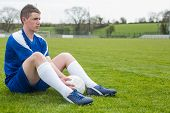 Football player in blue taking a break on the pitch on a clear day