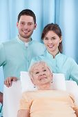stock photo of geriatric  - Closeup of two young physiotherapist and geriatric patient - JPG