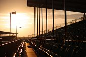 image of grandstand  - Symmetrical regular pattern grandstand seating arrangement at sunset - JPG