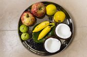 A plate with apple, guava, banana, citrus, betal leaves and coconut