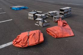 pic of tarp  - Orange tarp and broken boxes on a parking lot near the port - JPG