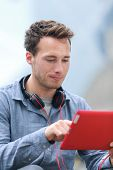 Urban young professional man using tablet computer sitting outside using app on 4g wireless device wearing headphones. Casual young urban professional male in his late 20s.