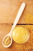 Composition of different kinds of mustard on wooden background
