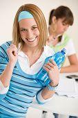 Estudante em casa - sorrindo mulher com garrafa de água