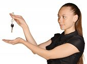 Beautiful girl broker holding sale house key. Looks at them