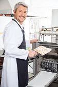 Side view portrait of happy chef using ravioli pasta machine at commercial kitchen