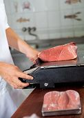 Cropped image of male butcher weighing meat on weight scale in shop