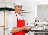 Portrait of smiling male chef standing by ravioli pasta machine at commercial kitchen