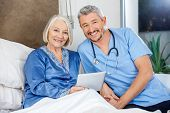 Portrait of happy senior woman and male caretaker with tablet PC in bedroom at nursing home