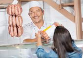Happy mature male butcher giving packed sausages to female customer in butchery