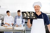 Portrait of smiling chef carrying baking sheet with dough balls while female colleagues working in background at commercial kitchen