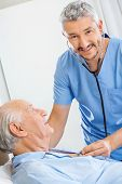 Portrait of happy male caretaker examining senior man with stethoscope in bedroom at nursing home