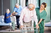 foto of retirement  - Happy female caretaker assisting senior man in using Zimmer frame at nursing home yard - JPG