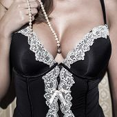 stock photo of tit  - Sexy woman with big tits holding pearls sensuality - JPG