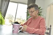 Elderly woman in nursing home reading book