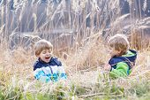 pic of bulrushes  - Two little sibling children fighting and having fun with bulrush near forest lake nature on cold spring or autumn day - JPG