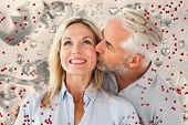 Affectionate man kissing his wife on the cheek against grey valentines heart pattern
