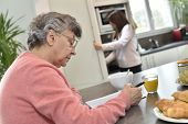 Elderly woman doing crosswords while homecare helps at home