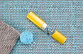 image of knitwear  - Brown knitwear with knitting needles and glasses are on the background of turquoise knitwear - JPG