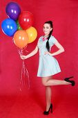 Portrait Of A Young Attractive Woman Holding Bunch Of Many Bright Balloons