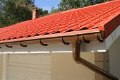 stock photo of gutter  - a corner of a house with gutters and metal roof - JPG