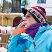 Woman in ski resort using smartphone.
