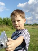 Little boy with toy-pistol poster