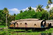 stock photo of alleppey  - Coco trees reflection and beautifoull house boat at back waters of Kerala India - JPG